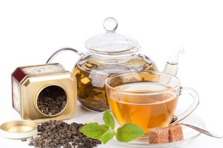 scented: Teapot and cup of tea  with mint on a white background. Stock Photo