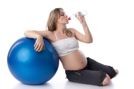 The young sports pregnant woman sits near a gymnastic ball on a white background. Care of health and pregnancy. Stock Photo - 7530468