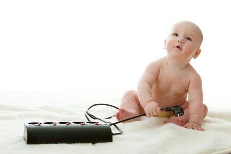 toma corriente: Dulce beb� peque�o con enchufe el�ctrico sobre un fondo blanco.  Foto de archivo