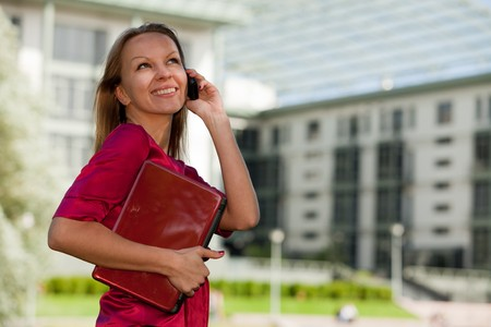 Beautiful business woman with laptop and mobile phone stands in the street. Stock Photo - 7530483