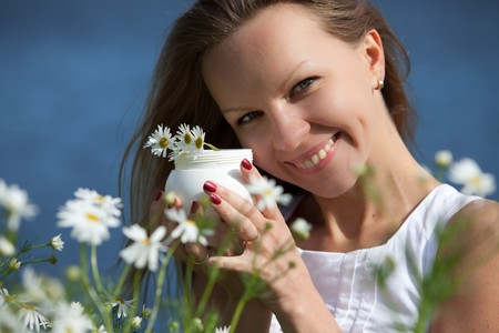 The young woman with cosmetic cream among camomiles on outdoors. photo