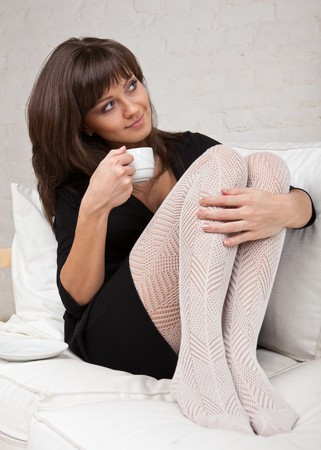 black stockings: Attractive young woman lying on a white sofa with cup of coffee. Stock Photo