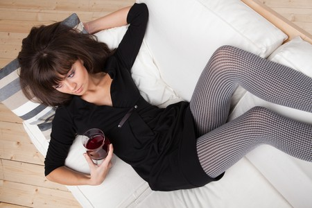 Young woman relaxes at home on the white sofa with a glass of red wine Stock Photo - 7638592