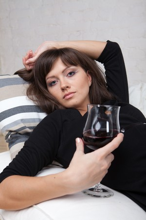 relaxes: Mujer joven se relaja en casa en el sof� blanco con un vaso de vino tinto