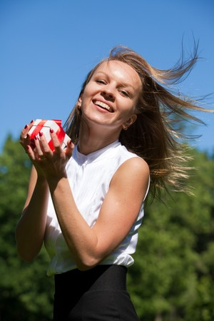 Young happy woman with a gift in the park in sunny day. Stock Photo - 7686021