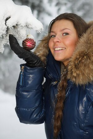 The beautiful Christmas girl decorates a fur-tree in winter wood. Stock Photo - 7845674