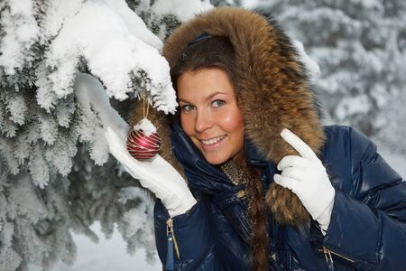 The beautiful Christmas girl decorates a fur-tree in winter wood. Stock Photo - 7845682