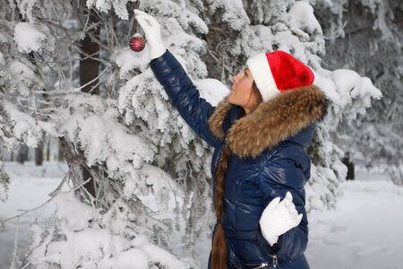 The beautiful girl in a Christmas cap decorates a fur-tree in winter wood. Stock Photo - 7845680