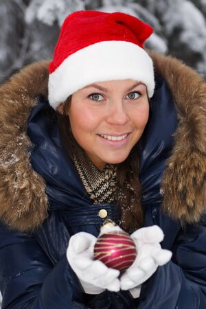 The beautiful girl in a Christmas cap decorates a fur-tree in winter wood. Stock Photo - 7845677