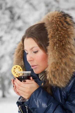 The beautiful girl drinks mulled wine in winter wood. photo