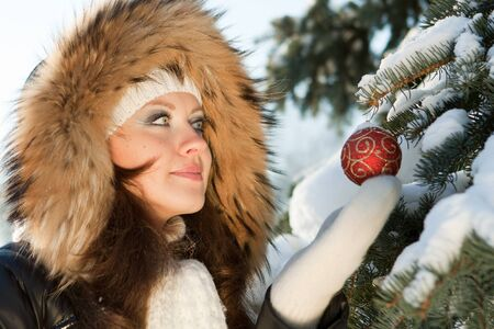The beautiful Christmas girl decorates a fur-tree in winter wood. Stock Photo - 7845683