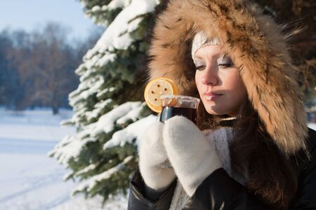 The beautiful girl drinks mulled wine in winter wood.