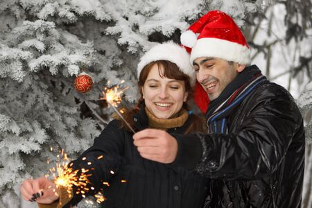 Young couple with bengal firework in the winter forest. Christmas. Stock Photo