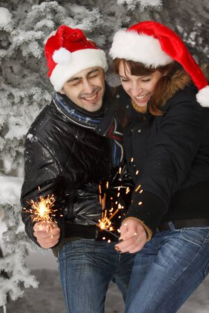 Young couple with bengal firework in the winter forest. Christmas. photo