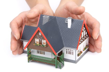 rental agency: Female hands with model of house on a white background. Concept  of buying and insuring  real estate.