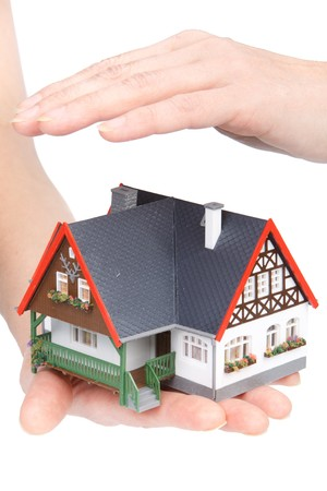 Female hands with model of house on a white background. Concept  of buying and insuring  real estate. photo