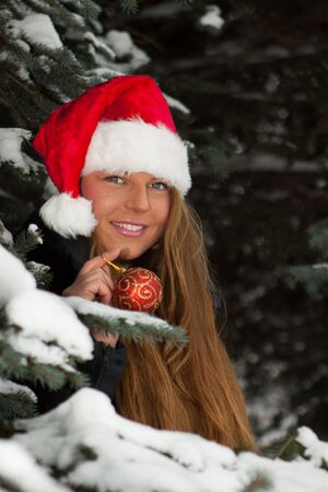 The beautiful girl in a Christmas cap decorates a fur-tree in winter wood. Stock Photo - 8032610