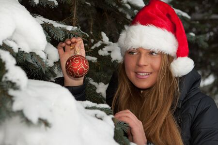 The beautiful girl in a Christmas cap decorates a fur-tree in winter wood. Stock Photo - 8032612