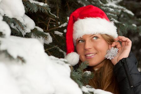 The beautiful girl in a Christmas cap decorates a fur-tree in winter wood. Stock Photo - 8032613