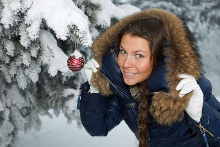 The beautiful Christmas girl decorates a fur-tree in winter wood. Stock Photo - 8107671