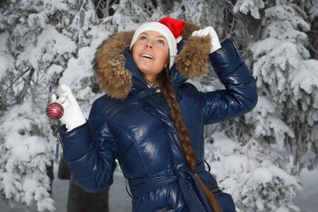 The beautiful girl in a Christmas cap decorates a fur-tree in winter wood. Stock Photo - 8107666