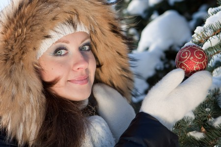 The beautiful Christmas girl decorates a fur-tree in winter wood. Stock Photo - 8107672