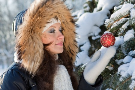 The beautiful Christmas girl decorates a fur-tree in winter wood. photo