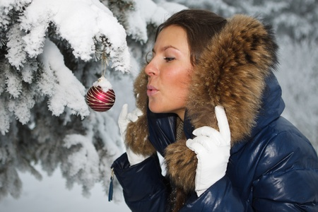 The beautiful Christmas girl decorates a fur-tree in winter wood. Stock Photo - 8359722