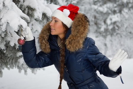 The beautiful girl in a Christmas cap decorates a fur-tree in winter wood. photo