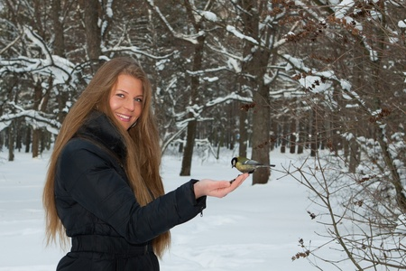 The beautiful girl feeds a bird in winter snow-covered park. photo
