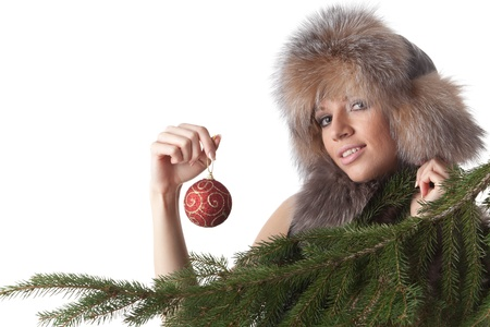 The young woman in furs decorates a Christmas fur-tree on a white background. photo