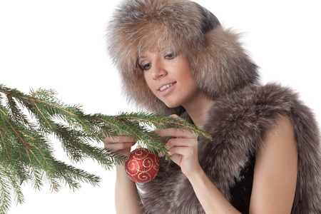 The young woman in furs decorates a Christmas fur-tree on a white background. Stock Photo - 8359738