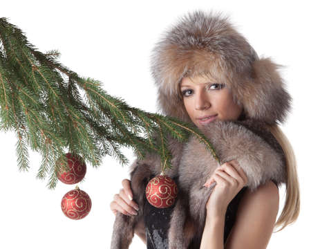 The young woman in furs decorates a Christmas fur-tree on a white background. Stock Photo - 8359737