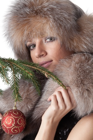 The young woman in furs decorates a Christmas fur-tree on a white background. Stock Photo - 8359739