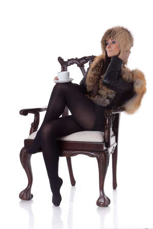 Young woman in fur with cup of coffee sit on armchair on a white background. photo