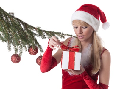 The beautiful girl with a gift in a Santa's cap stands near a Christmas tree on a white background. Stock Photo - 8405480