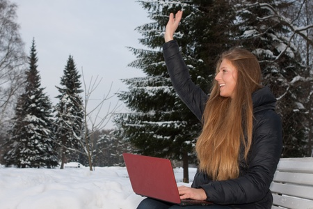 The beautiful girl with the laptop sits on a bench in winter park. photo