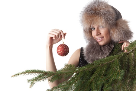 The young woman in furs decorates a Christmas fur-tree on a white background. Stock Photo - 8452458
