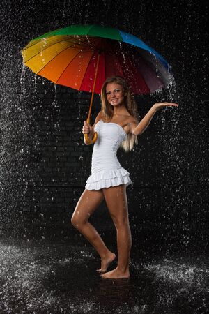 Young pretty woman with multi-coloured umbrella under rain on a black background. Stock Photo - 8482325