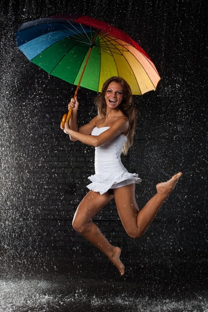 Young pretty woman with multi-coloured umbrella under rain on a black background. Stock Photo - 8475354