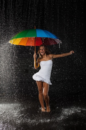 Young pretty woman with multi-coloured umbrella under rain on a black background. Stock Photo - 8475353