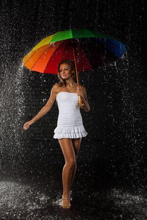 brolly: Mujer joven y bonita con paraguas multicolor bajo lluvia sobre un fondo negro.
