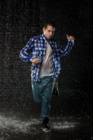 Young man dancing in water under rain on a black background.  Modern dances. photo