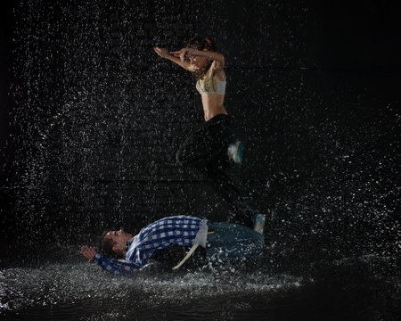 Jong koppel dansen in water onder de regen op een zwarte achtergrond.  Moderne dansen. Stockfoto