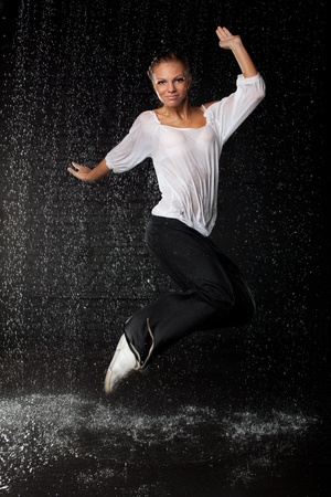 The beautiful girl dancing in water under rain on a black background.  Modern dances. Stock Photo - 8482302