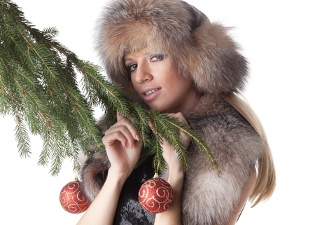 The young woman in furs decorates a Christmas fur-tree on a white background. Stock Photo - 8489065