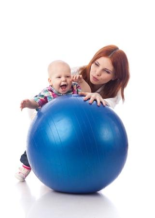 Madre y el bebé pequeño dulce con bola de fitness sobre un fondo blanco.