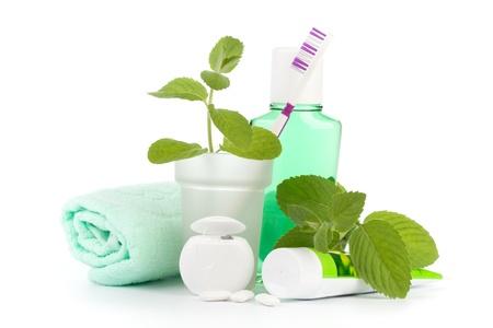 limpieza: Cepillo de dientes con pasta de dientes y frescas hojas de menta, sobre un fondo blanco.