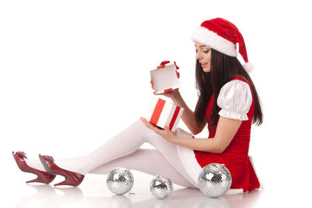 The beautiful young woman in a Santa's cap  with a gift  on a white background. Stock Photo - 8543406