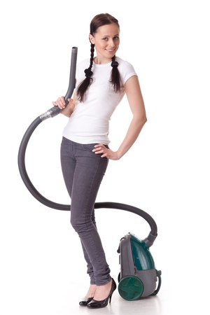 Young woman with vacuum cleaner on a white background. Housekeeping.
